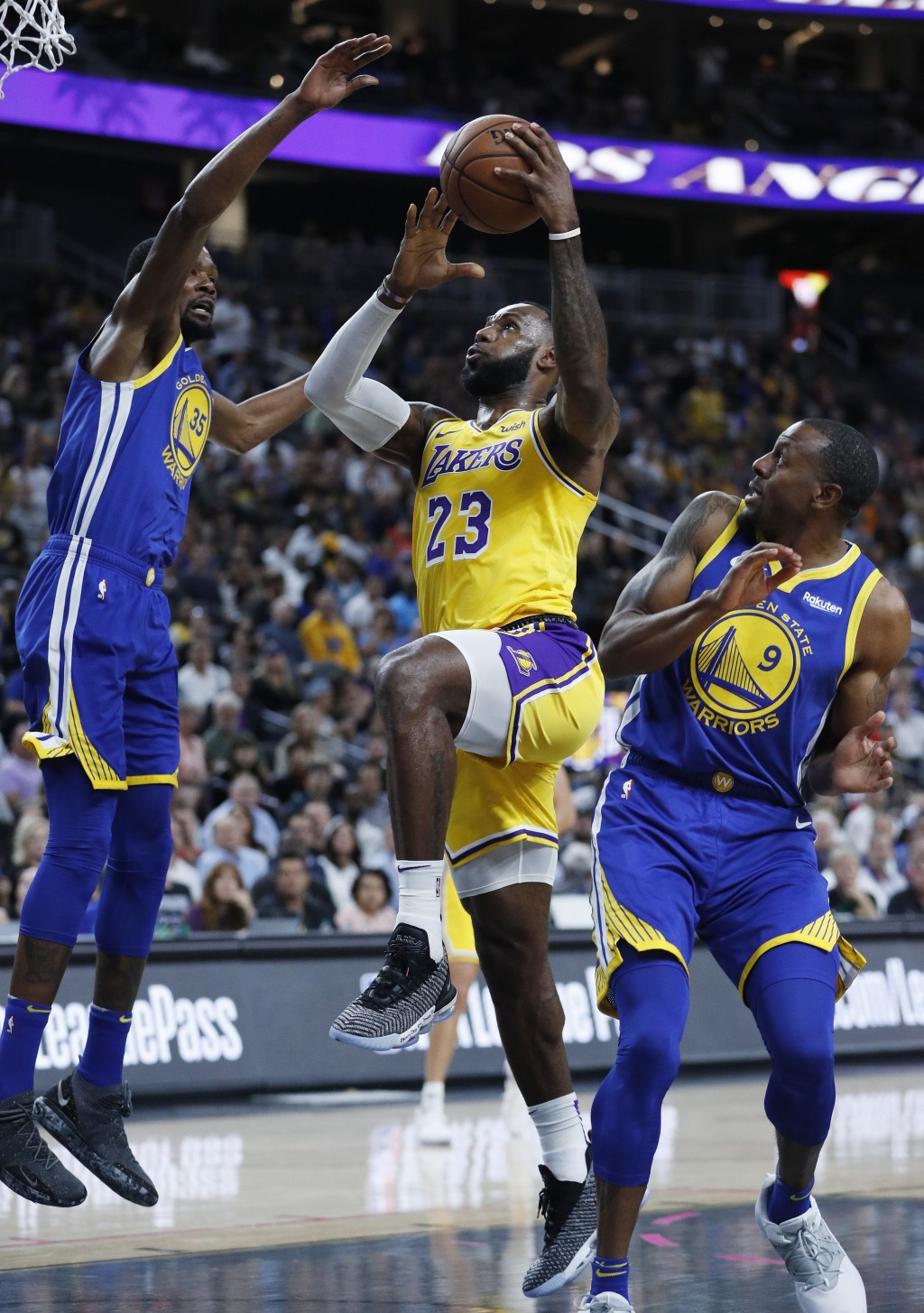 Los Angeles Lakers forward LeBron James (23) shoots between Golden State Warriors forward Kevin Durant, left, and guard Andre Iguodala during the firs