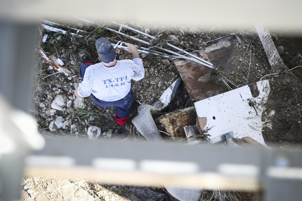 Texas Task Force 1 member walks through debris to find the missing people after the South Llano River flooding Wednesday, Oct. 10, 2018, in Junction,