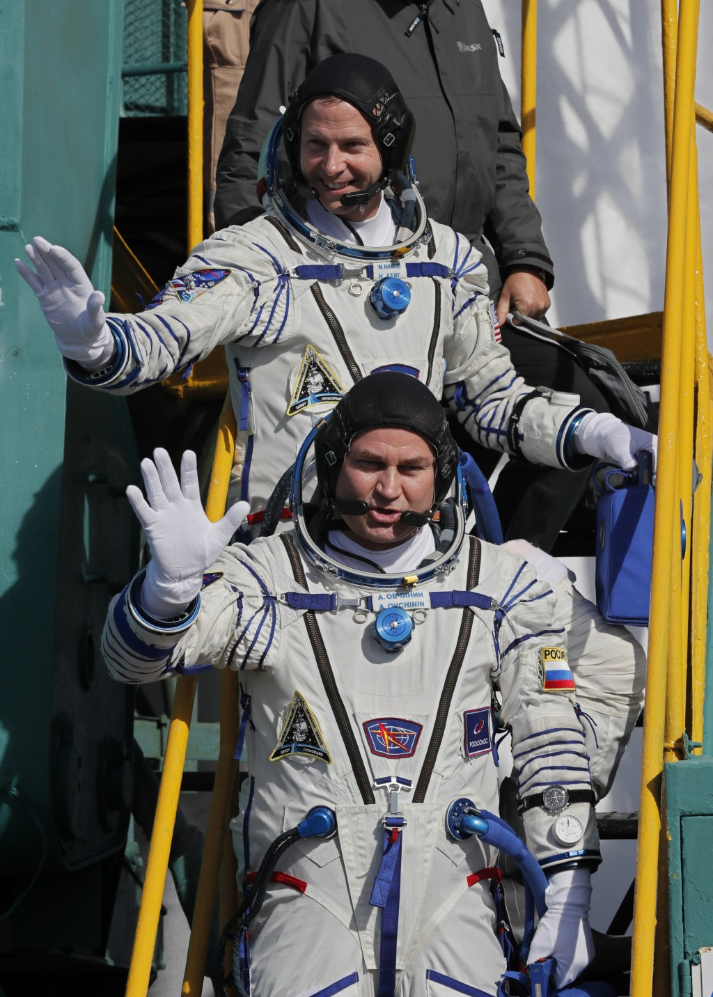 U.S. astronaut Nick Hague, top, and Russian cosmonaut Alexey Ovchinin, crew members of the mission to the International Space Station, ISS, wave as th