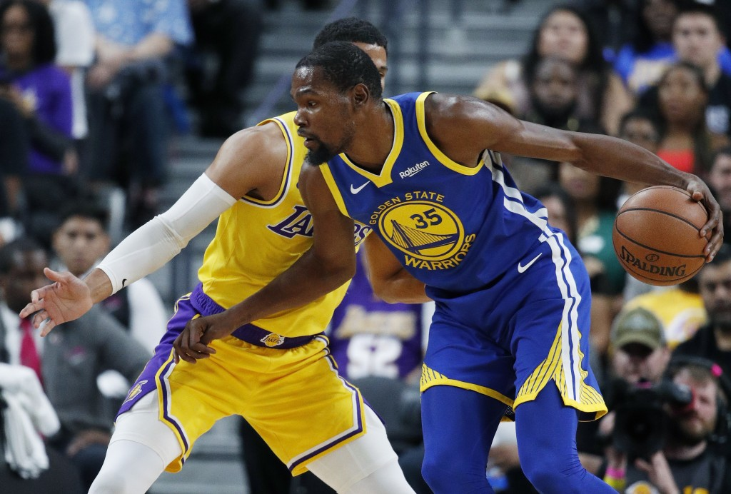 Golden State Warriors forward Kevin Durant drives against Los Angeles Lakers guard Josh Hart during the first half of an NBA preseason basketball game