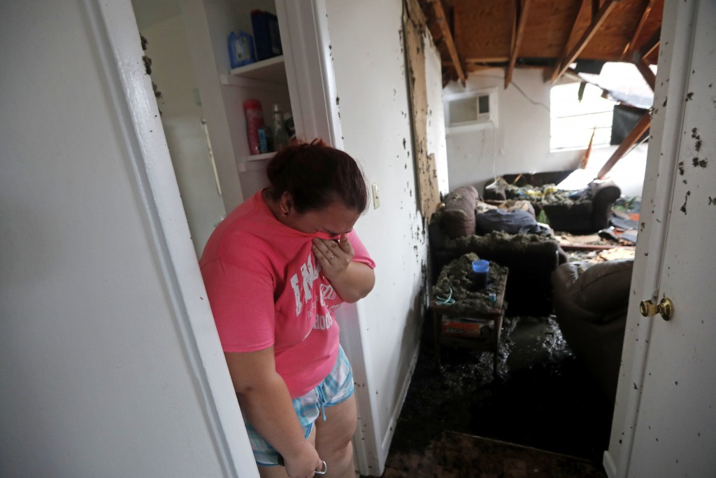 Kaylee O'Brian weeps inside her home after several trees fell on it during Hurricane Michael in Panama City, Fla., Wednesday, Oct. 10, 2018. (AP Photo