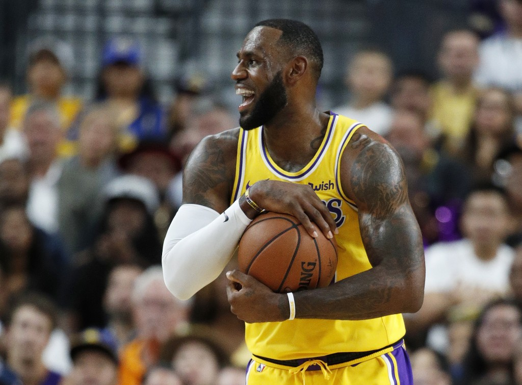 Los Angeles Lakers forward LeBron James reacts after a play against the Golden State Warriors during the first half of an NBA preseason basketball gam