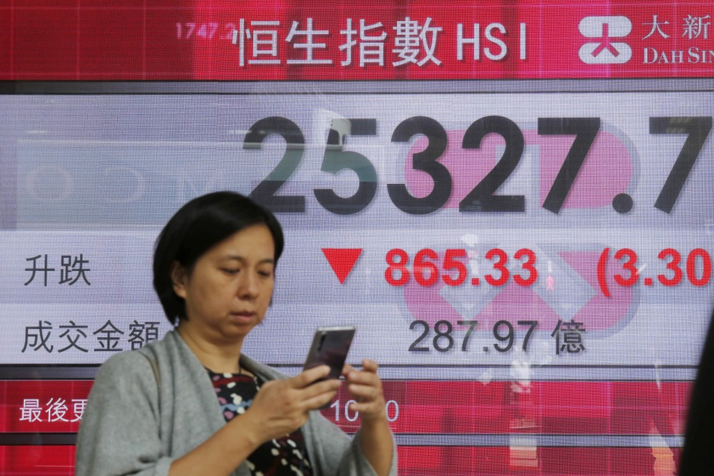 A woman walks past an electronic board showing Hong Kong share index outside a bank In Hong Kong, Thursday, Oct. 11, 2018. Asian markets tumbled on Th