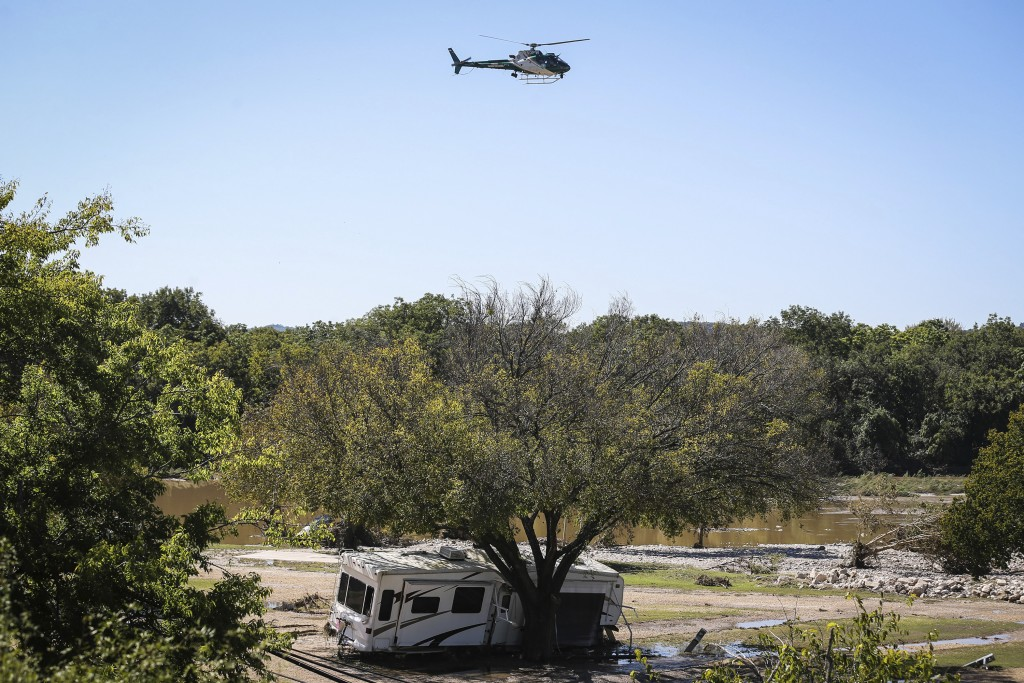 Search and rescue helicopter flies by the RV park hit in Monday's South Llano River flooding Wednesday, Oct. 10, 2018, in Junction, Texas.  (Yfat Yoss