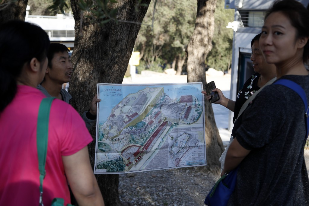 Tourists guides show a map of the Acropolis to tourists in Athens, Thursday, Oct. 11, 2018 during a 24-hour strike called by a Greek union representin
