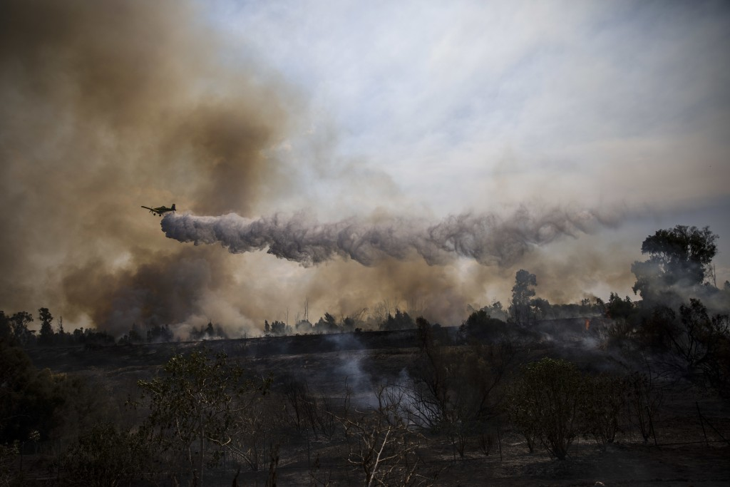 A firefighting plane passes over a fire started by a balloon with attached burning cloth launched by Palestinians from Gaza Strip in Karmia nature res