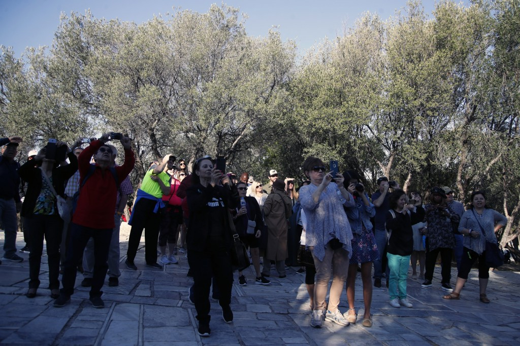 Tourists take photographs outside the closed Acropolis ancient site in Athens, Thursday, Oct. 11, 2018 during a 24-hour strike called by a Greek union
