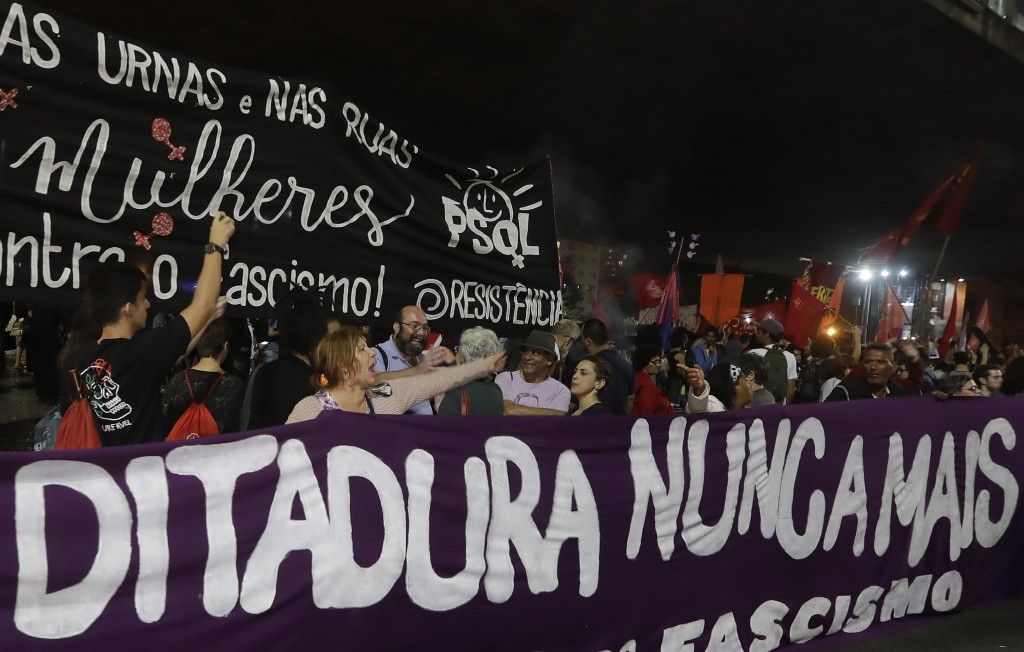 "Demonstrators carry a banner that reads in Portuguese ""Dictatorship never again,"" during a protest against Jair Bolsonaro, a far-right presidential ca"
