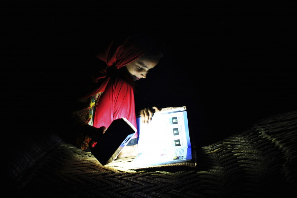 In this Friday, August 10, 2018, photo, Ansa Khan studies with a flash light during a power outage in Mardan, Pakistan. Ansa enjoys her school, saying