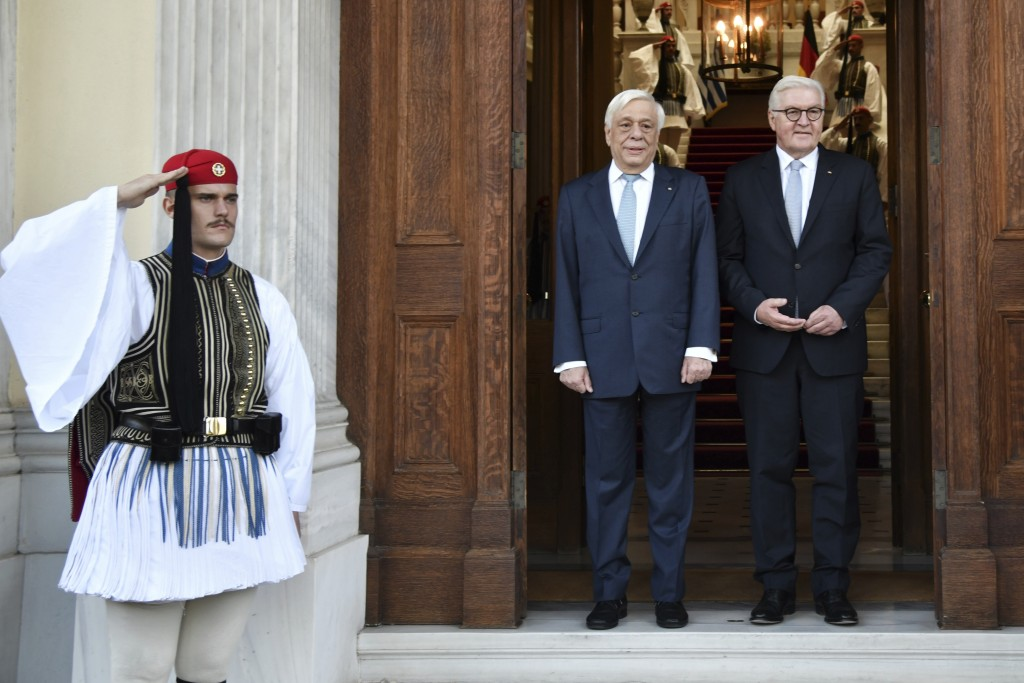 Greek President Prokopis Pavlopoulos welcomes German President Frank-Walter Steinmeier, right, at the Presidential Palace in Athens, Thursday, Oct. 11