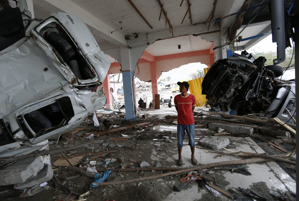 A man inspects the wreckage of vehicles inside a building at the tsunami-ravaged area in Palu, Central Sulawesi, Indonesia, Thursday, Oct. 11, 2018. A