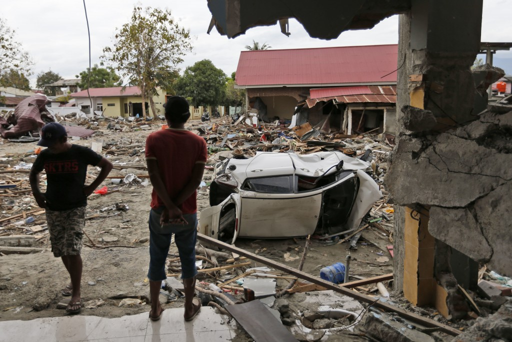 Men view the damage at a tsunami-ravaged area in Palu, Central Sulawesi, Indonesia, Thursday, Oct. 11, 2018. A 7.5 magnitude earthquake rocked Central