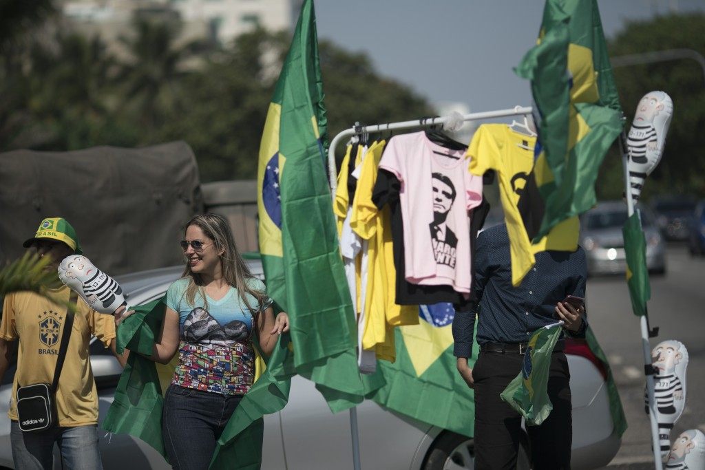 A supporter of presidential candidate Jair Bolsonaro of the Social Liberal Party, buys a Brazilian flag being sold in front of the entrance of Bolsona