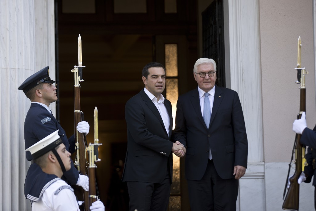 Greek Prime Minister Alexis Tsipras, left, welcomes German President Frank-Walter Steinmeier, before their meeting in Athens, on Wednesday, Oct. 11, 2