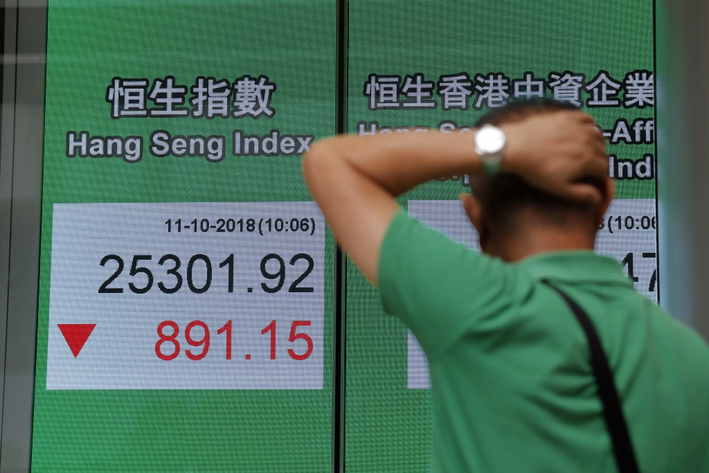 A man looks at an electronic board showing Hong Kong share index outside a bank In Hong Kong, Thursday, Oct. 11, 2018. Asian markets tumbled on Thursd