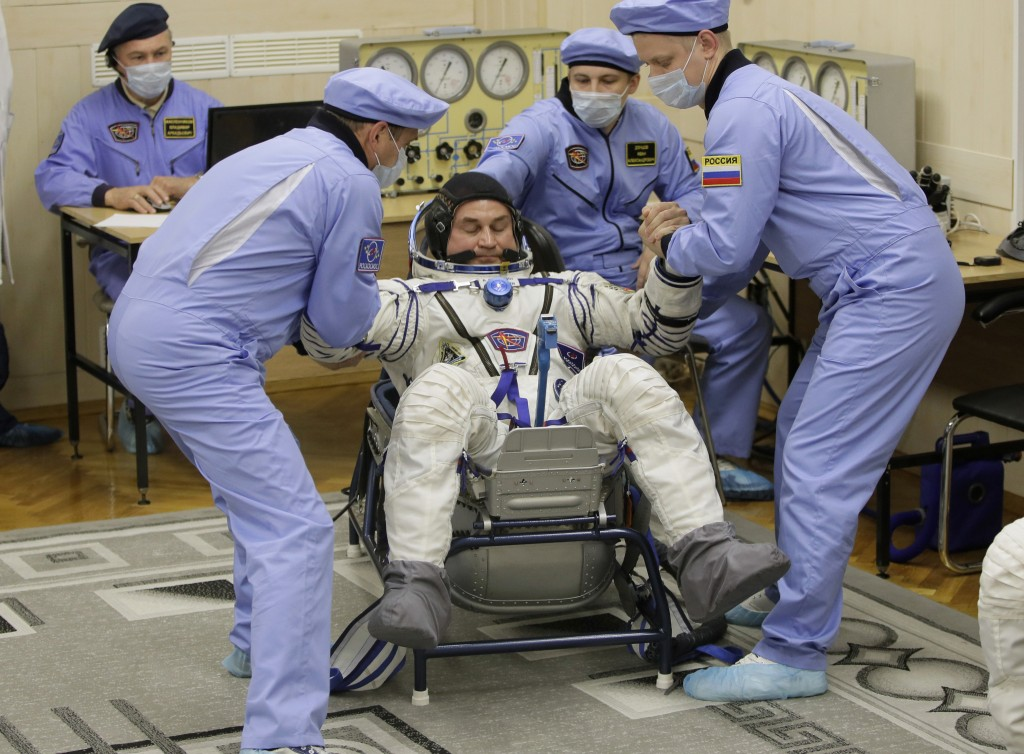 Russian Space Agency experts help Russian cosmonaut Alexey Ovchinin, a member of the main crew of the expedition to the International Space Station (I