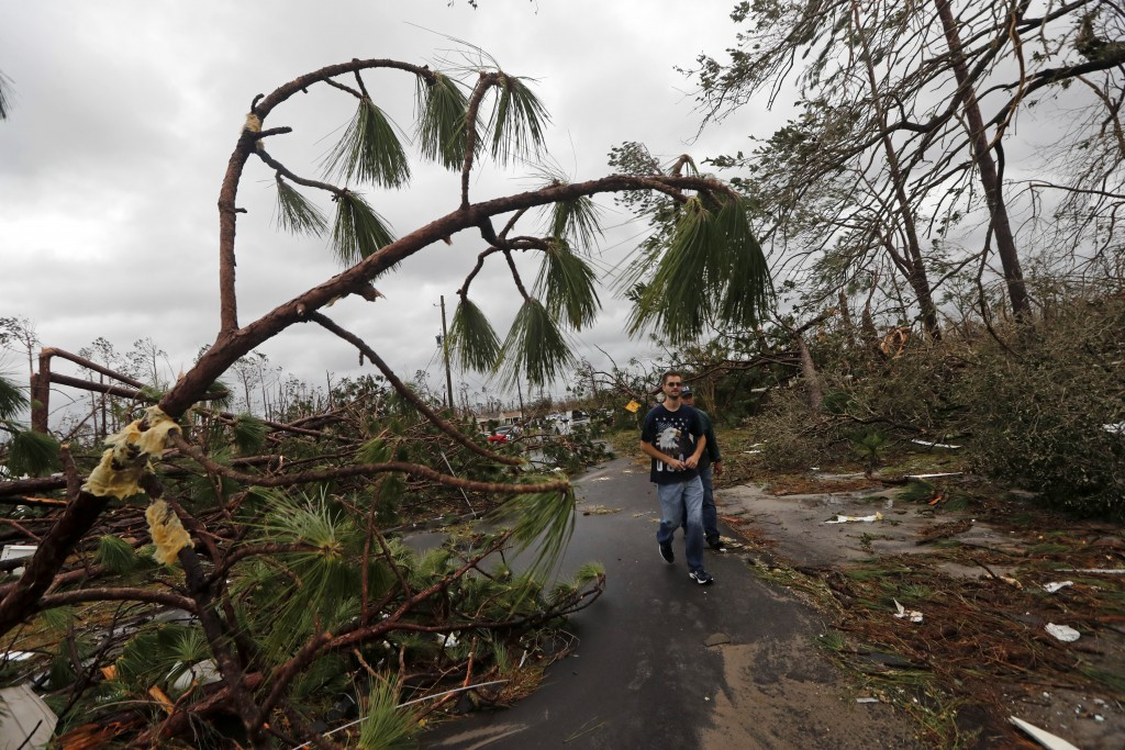 People walk through downed trees in a heavily damaged neighborhood in the aftermath of Hurricane Michael in Panama City, Fla., Wednesday, Oct. 10, 201