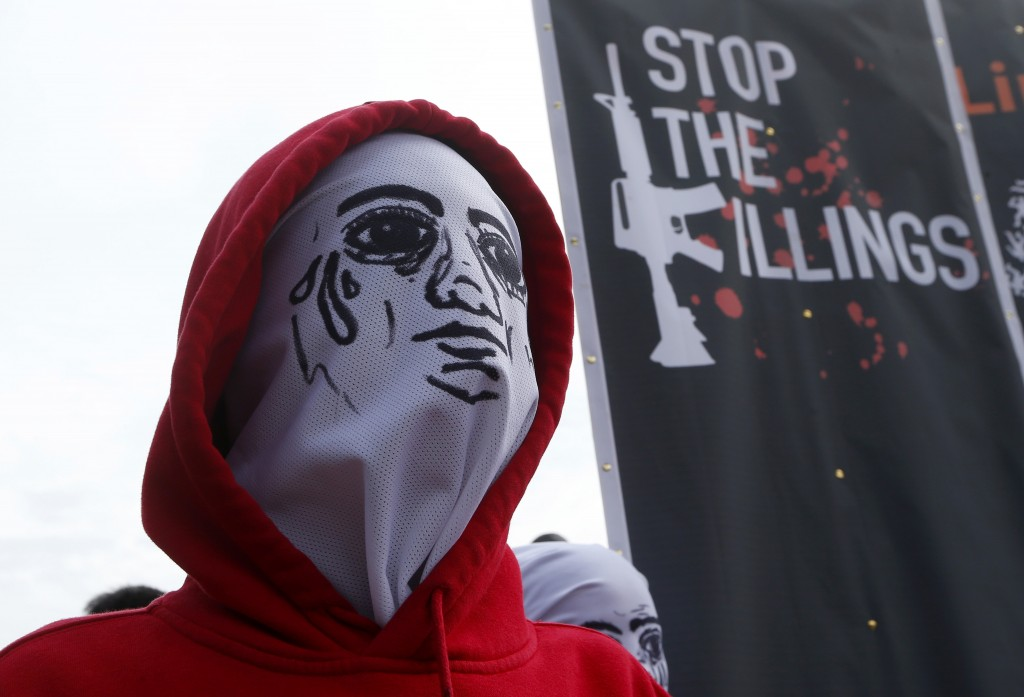 FILE - In this July 23, 2018 file photo, a masked demonstrator stands next to a banner protesting the thousands of victims of Philippine President Rod