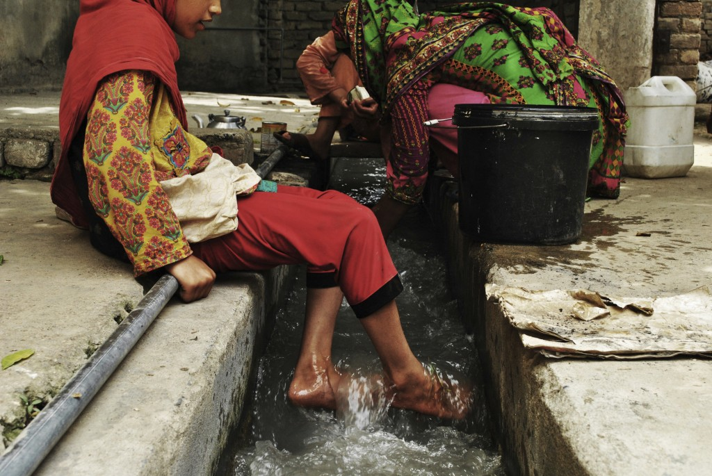 In this Monday, July 9, 2018, photo, Ansa Khan cools her feet with running water just adjacent to her home while her mother and sister are busy in the
