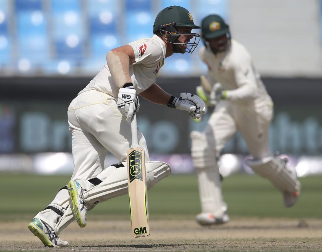 Australia's Travis Head, left, and Usman Khawaja run between the wickets during their test match against Pakistan in Dubai, United Arab Emirates, Thur