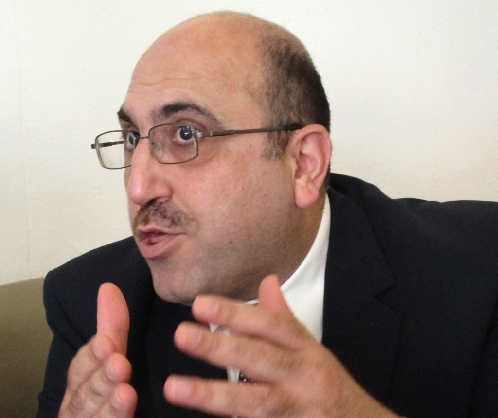 FILE - In this Oct. 10, 2013 file photo, exiled Syrian Rami Abdurrahman, who operates the Syrian Observatory for Human Rights from Coventry, gives an