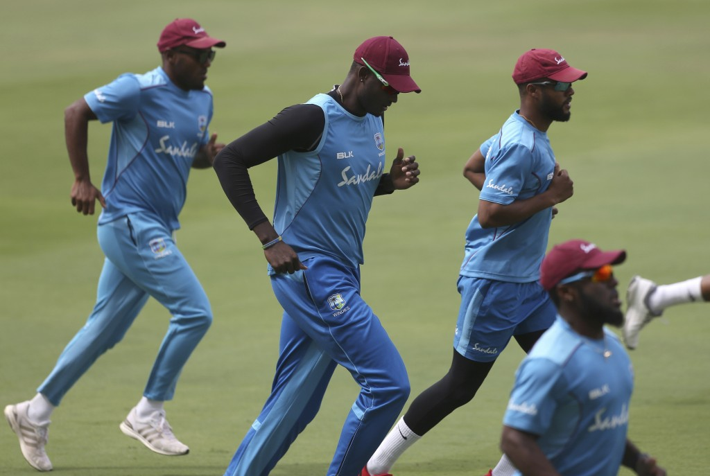 West Indies' cricket captain Jason Holder, center, along with teammates warmup during a practice session ahead of their second test match against Indi