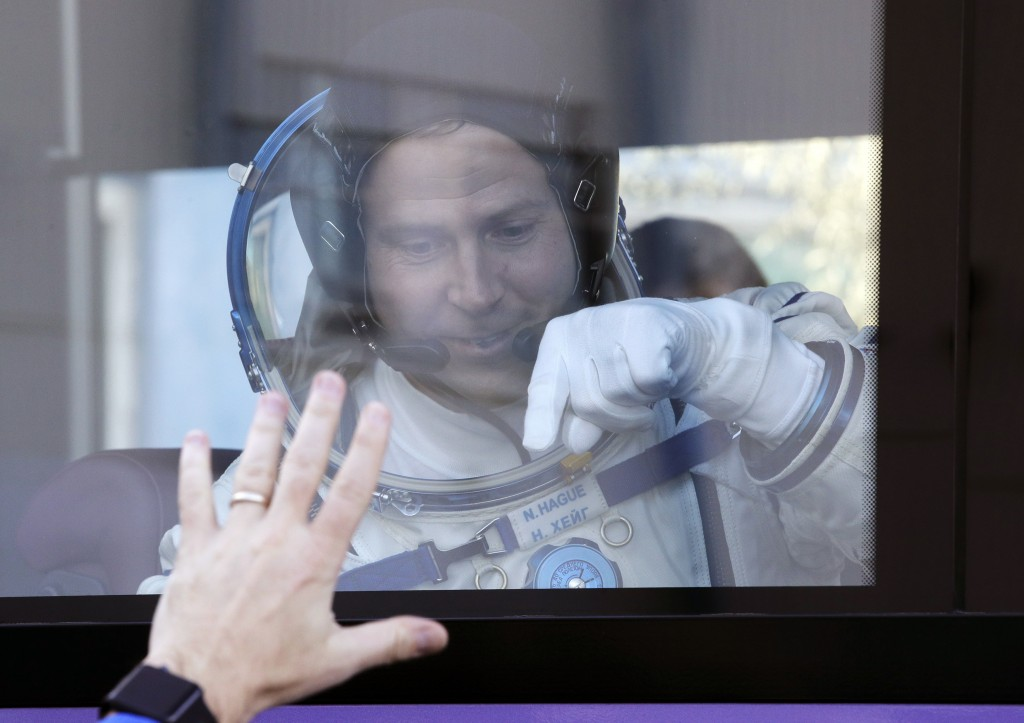 U.S. astronaut Nick Hague, member of the main crew to the International Space Station (ISS), waves to his relatives from a bus prior to the launch of