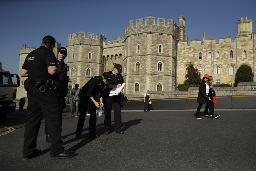 A police team check and seal a drain cover outside Windsor Castle ahead of the wedding of Britain's Princess Eugenie in Windsor, England, Wednesday, O