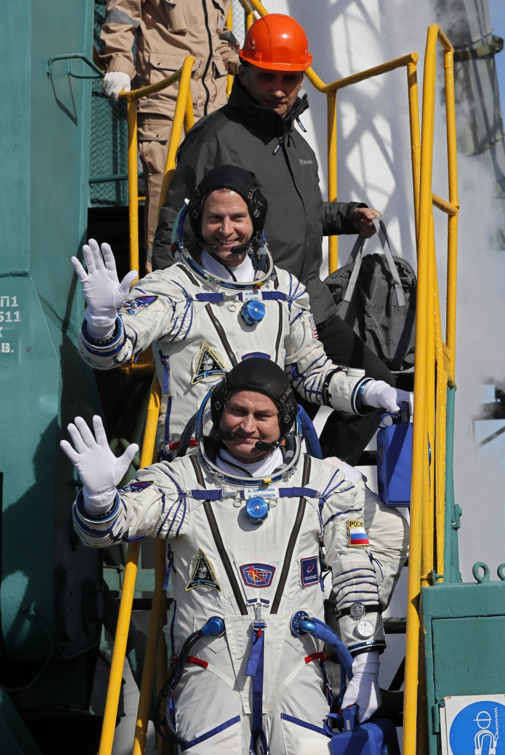 U.S. astronaut Nick Hague, right, and Russian cosmonaut Alexey Ovchinin, crew members of the mission to the International Space Station, ISS, wave as