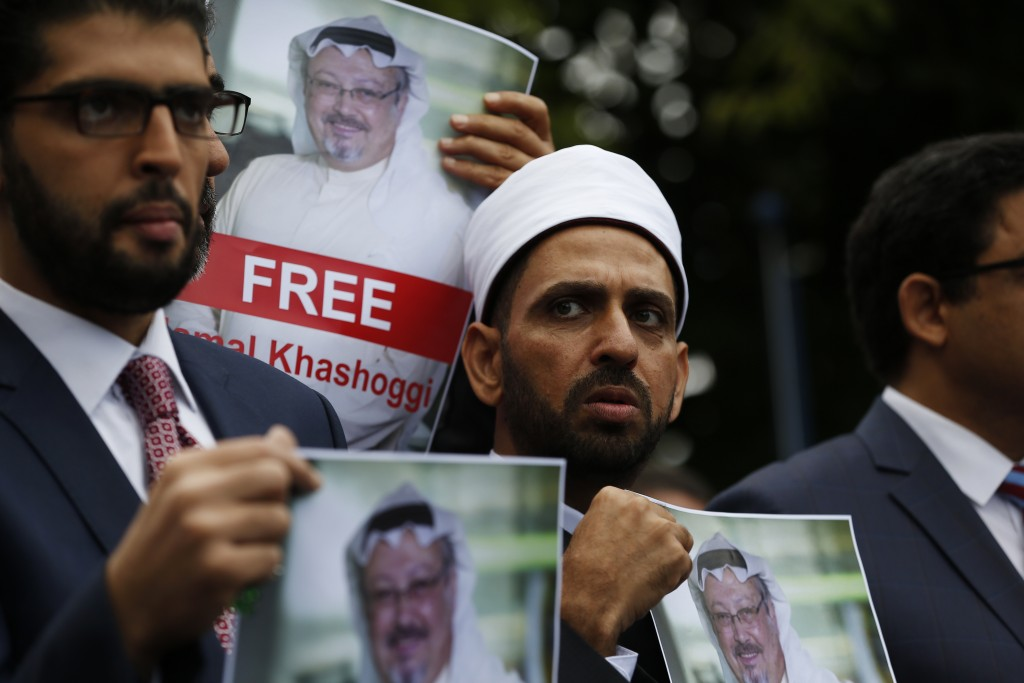 FILE - In this Monday, Oct. 8, 2018 file photo, members of the Turkish-Arab Journalist Association hold posters with photos of missing Saudi writer Ja