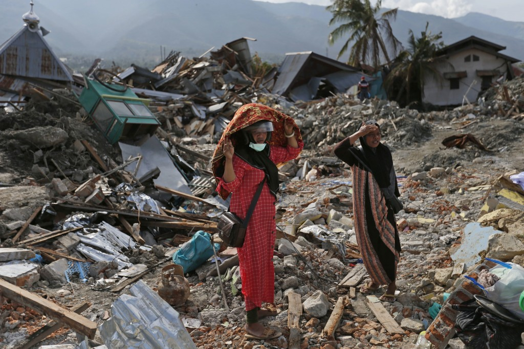 Indonesian women stand on the rubble as they look for what's left from a relative's house at Balaroa neighborhood in Palu, Central Sulawesi, Indonesia