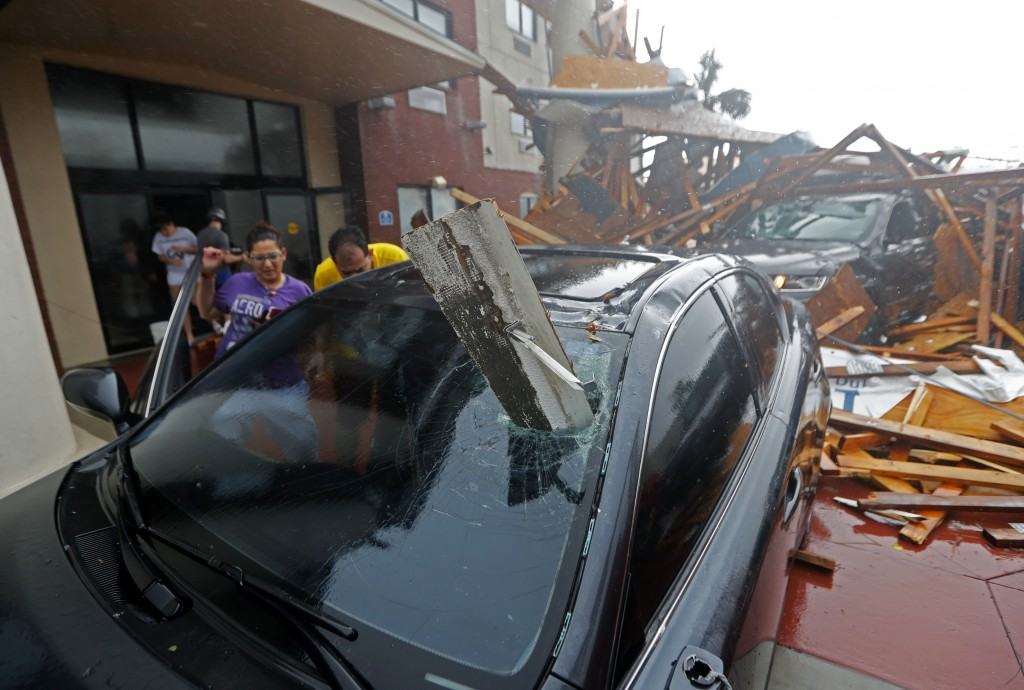 A woman checks on her vehicle as Hurricane Michael passes through, after the hotel canopy had just collapsed, in Panama City Beach, Fla., Wednesday, O