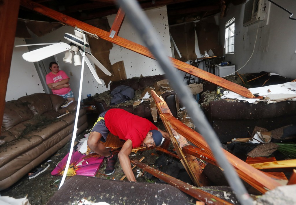 Dorian Carter looks under furniture for a missing cat after several trees fell on their home during Hurricane Michael in Panama City, Fla., Wednesday,