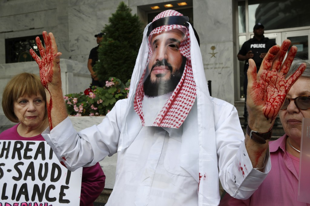 David Barrows, center, with Code Pink, wears a mask of Saudi Arabia Crown Prince Mohammed bin Salman during a protest outside of Saudi Arabia's Embass