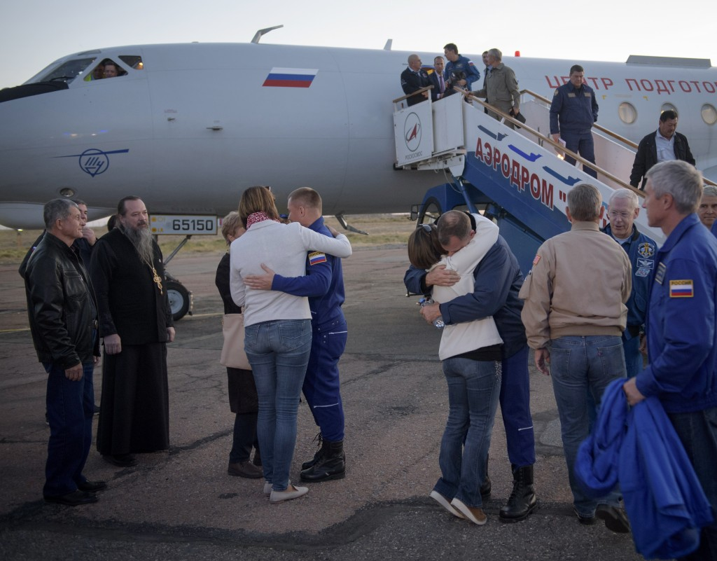 Expedition 57 Flight Engineer Alexey Ovchinin of Roscosmos, left, and Flight Engineer Nick Hague of NASA, right, embrace their families after landing