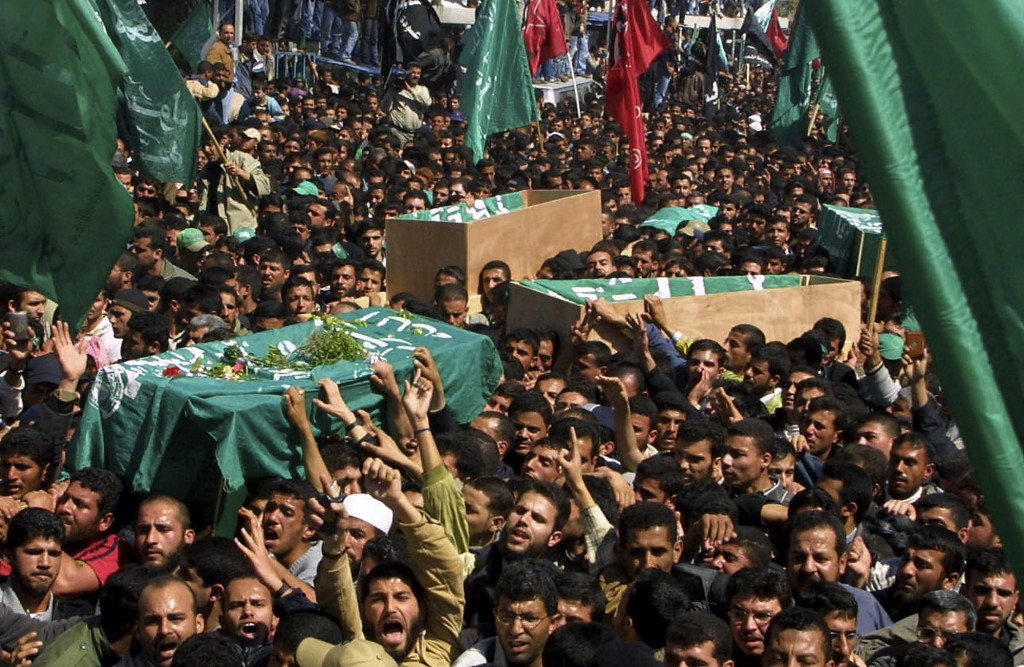 FILE - In this March 22, 2004 file photo, thousands of Palestinian mourners follow the coffin of Hamas spiritual leader Sheik Ahmed Yassin, during his