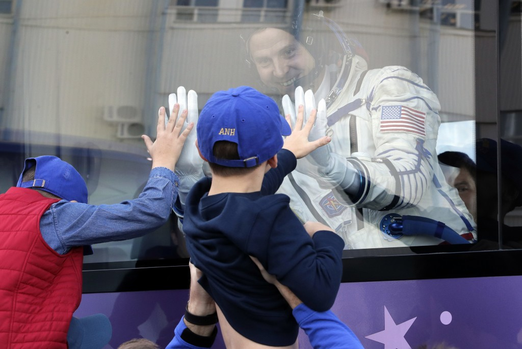 U.S. astronaut Nick Hague, member of the main crew to the International Space Station (ISS), waves to his sons from a bus prior to the launch of Soyuz