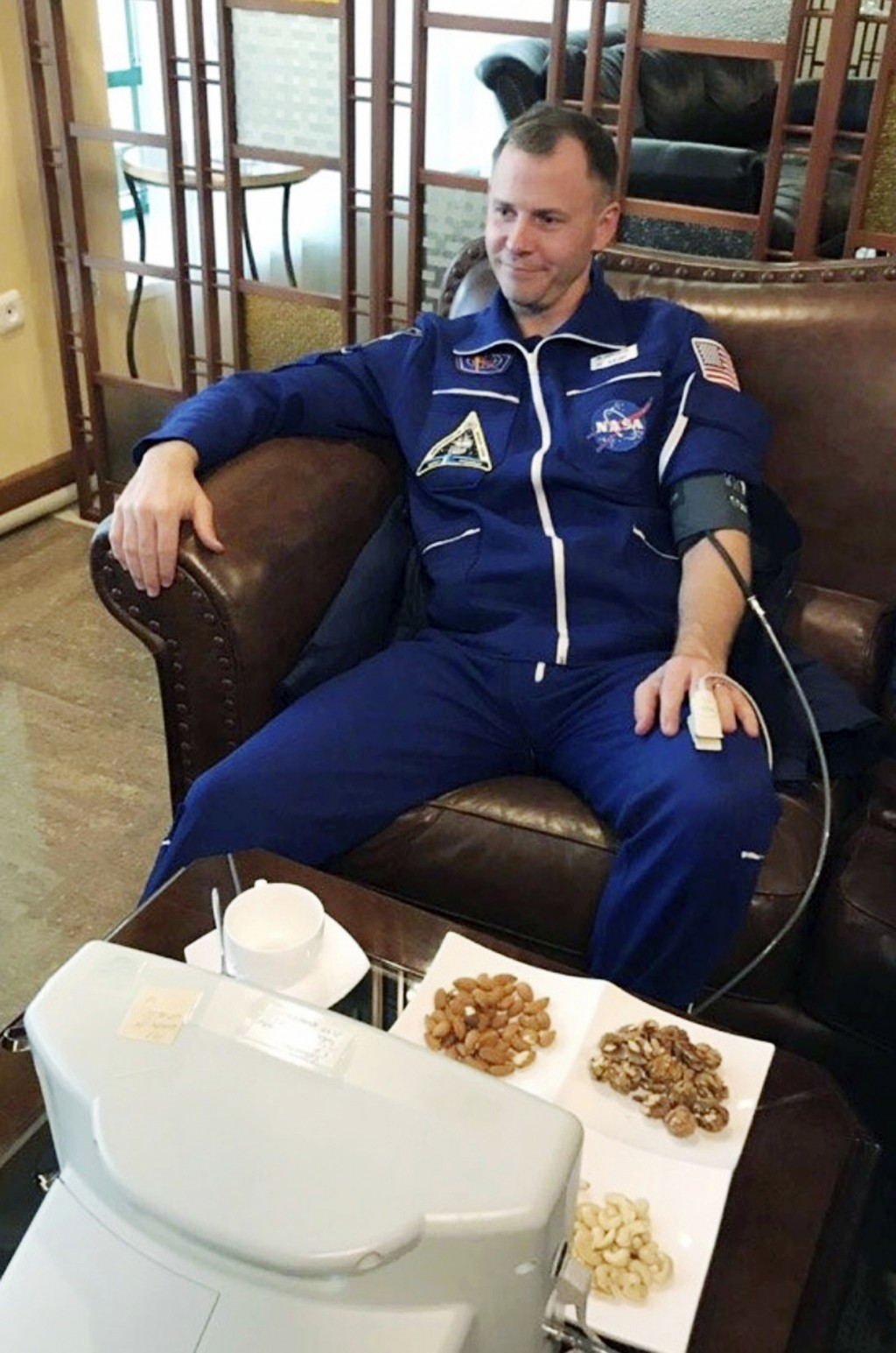 In this photo provided by Roscosmos, NASA astronaut Nick Hague sits in a hall after being transported by the rescue team, in Dzhezkazgan, about 450 ki