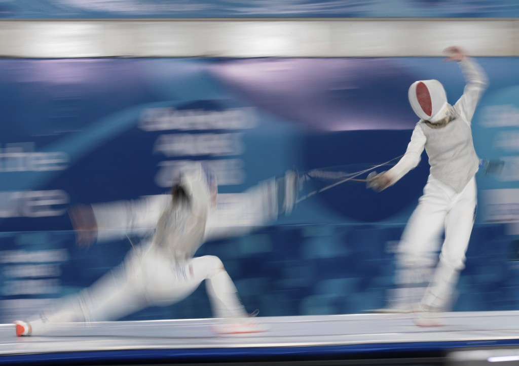 In this Wednesday, Oct. 10, 2018 photo, May Tieu of the U.S, left, and Venissia Thepaut of France, compete in the Fencing Mixed Continental Team Match