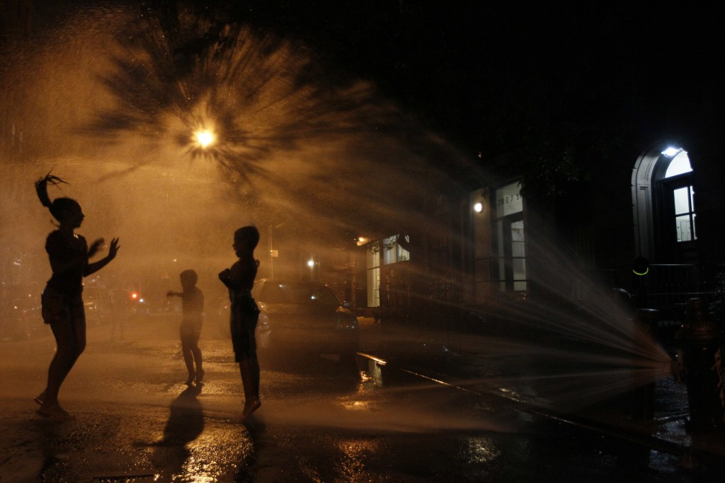 FILE - In this July 21, 2011, file photo, Vanity Mendez, 11, left, Isaiah Rivera, 6, center, and Jonathan Medina, 11, cool off at an open fire hydrant