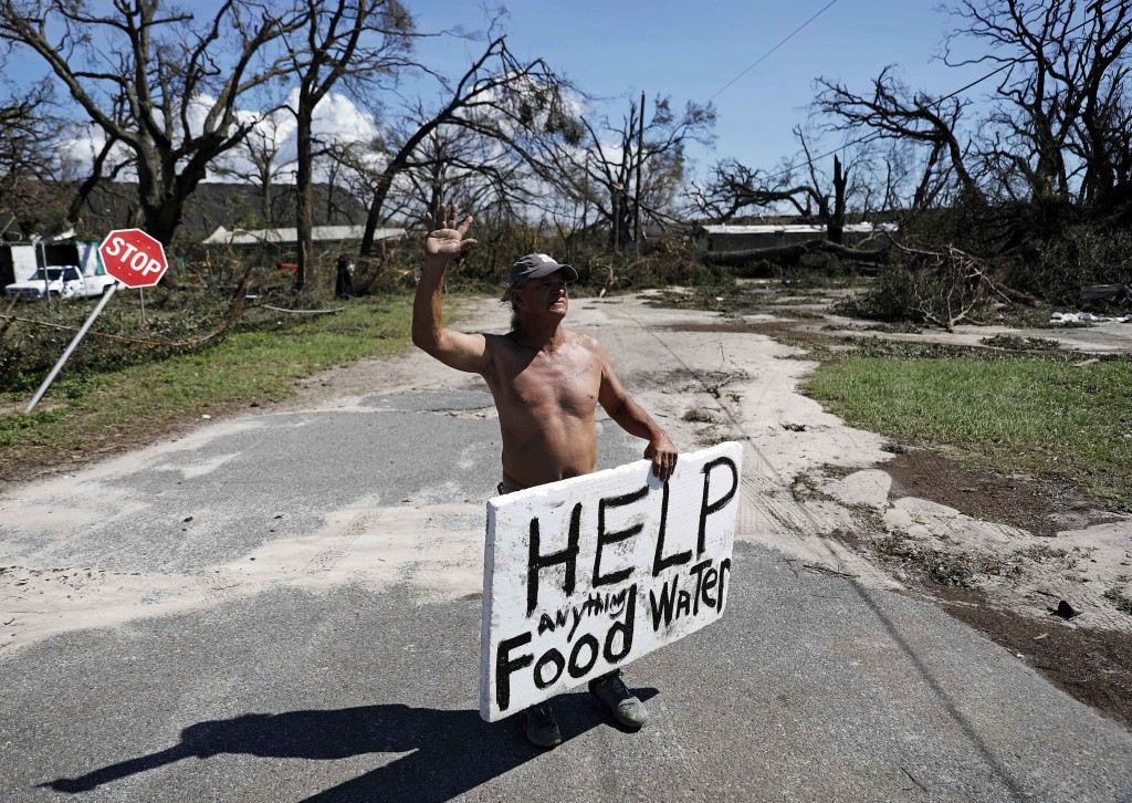 Michael Williams, 70, waves to passing motorists while looking for food and water as downed trees prevent him from driving out of his damaged home wit