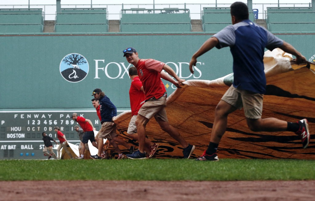 Fenway Park grounds crew pull a tarp over the field as it starts to rain during the Boston Red Sox's workout, Thursday, Oct. 11, 2018, in Boston. The