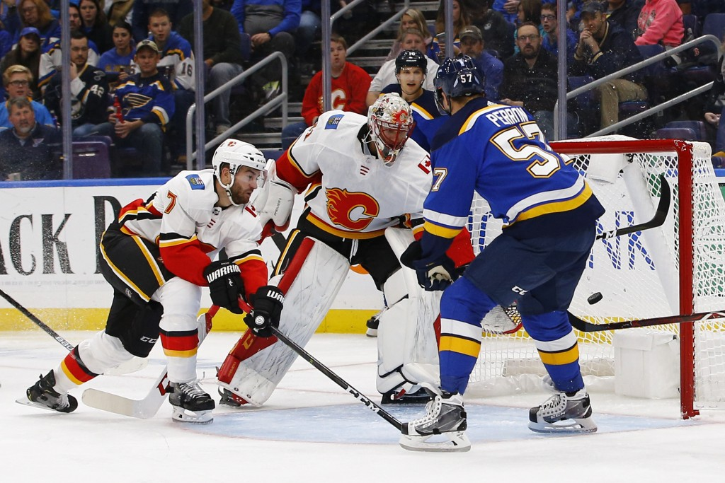 St. Louis Blues' David Perron, right, scores a goal against Calgary Flames goaltender Mike Smith as TJ Brodie defends during the second period of an N