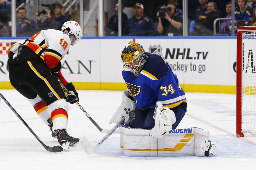 St. Louis Blues goaltender Jake Allen, right, makes a save on a shot by Calgary Flames' James Neal during the first period of an NHL hockey game Thurs