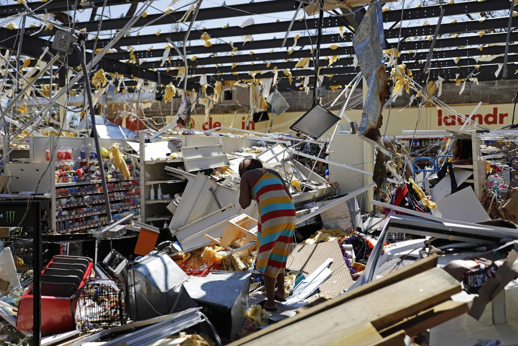 A woman walks through a damaged store in the aftermath of Hurricane Michael in Springfield, Fla., Thursday, Oct. 11, 2018. (AP Photo/David Goldman)