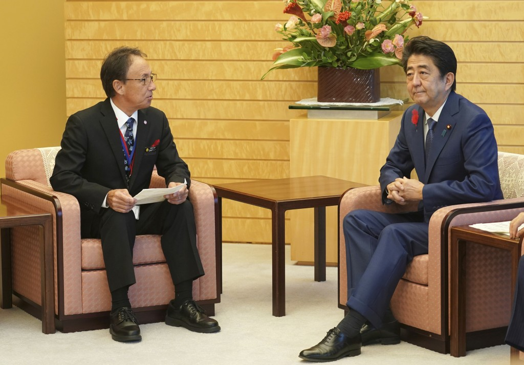 Okinawa Governor Denny Tamaki, left, meets with Japanese Prime Minister Shinzo Abe at Abe's office in Tokyo Friday, Oct. 12, 2018. Tamaki won the elec