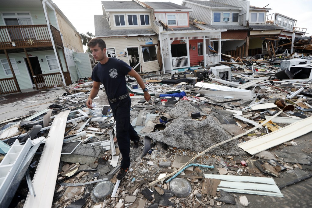 Firefighter Austin Schlarb performs a door to door search in the aftermath of Hurricane Michael in Mexico Beach, Fla., Thursday, Oct. 11, 2018. (AP Ph