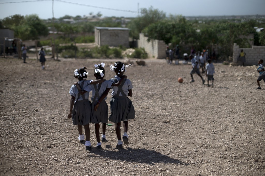FILE - In this June 24, 2015, file photo, schoolgirls walk through the rocky yard of Bethesda Evangelical School during a break in class, in Canaan, H