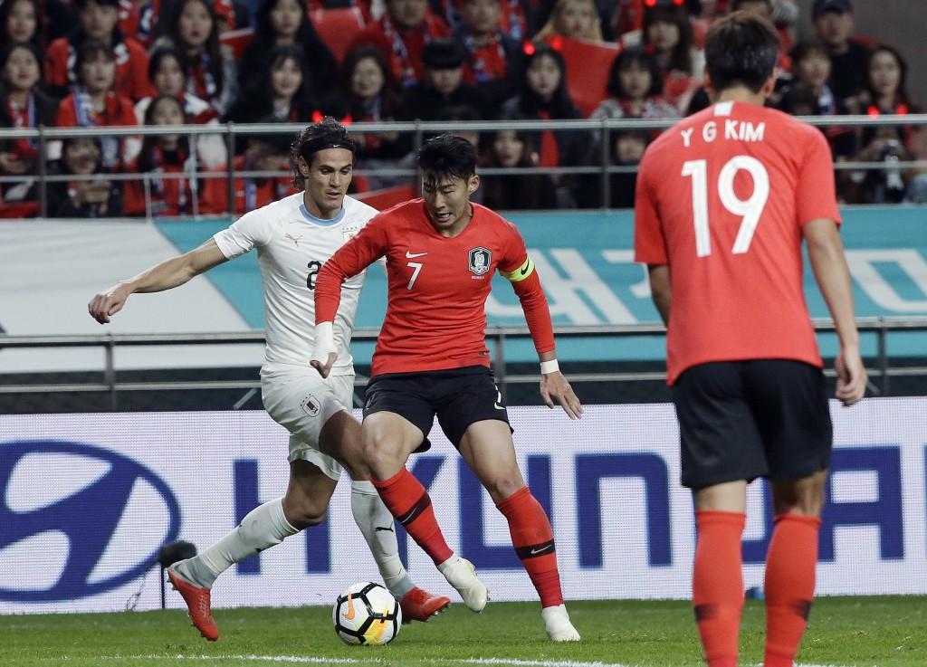 South Korea's Son Heung-min fights for the ball against Uruguay's Edinson Cavani, left, during their friendly soccer match in Seoul, South Korea, Frid