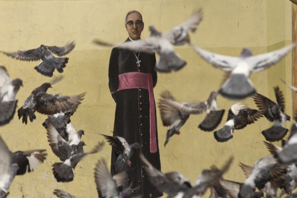 In this Oct. 3. 2018 photo, pigeons fly in front of a mural of Archbishop Oscar Arnulfo Romero, on a wall of the Metropolitan Cathedral in San Salvado